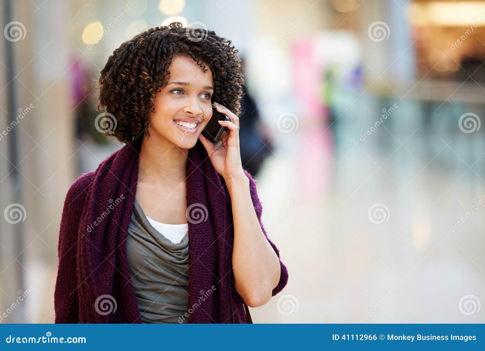 Kobieta W zakupy centrum handlowym Używać telefon komórkowego