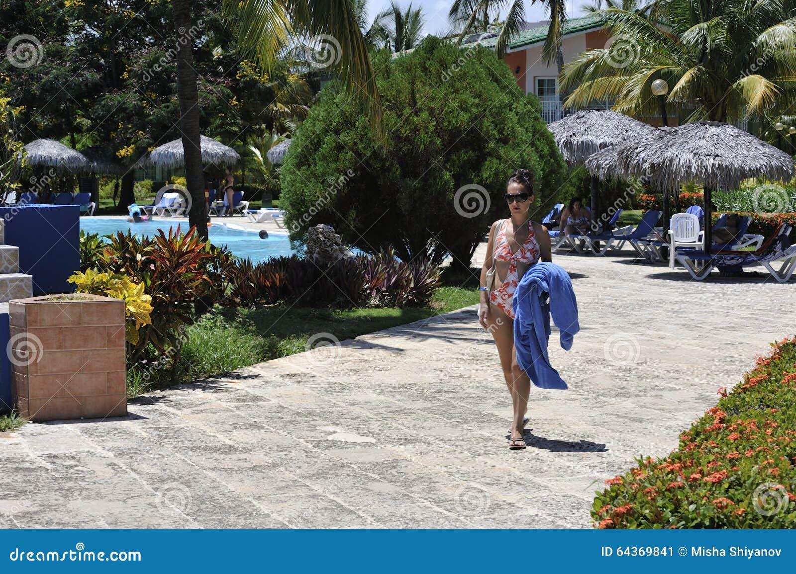Kobieta w zdroju kurorcie w pływackim kostiumu bierze słońce kąpać się