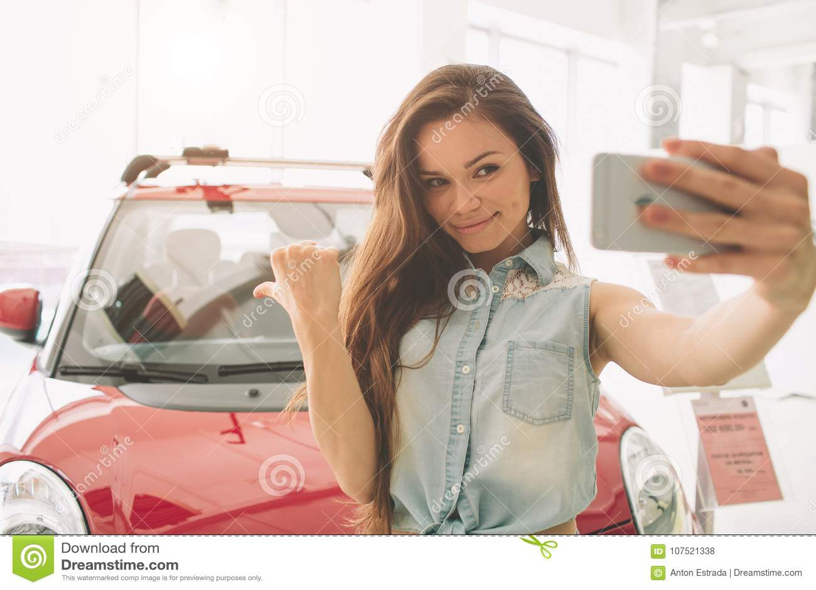 Kobieta wp8lywy selfie w nowym samochodzie przy sala wystawową