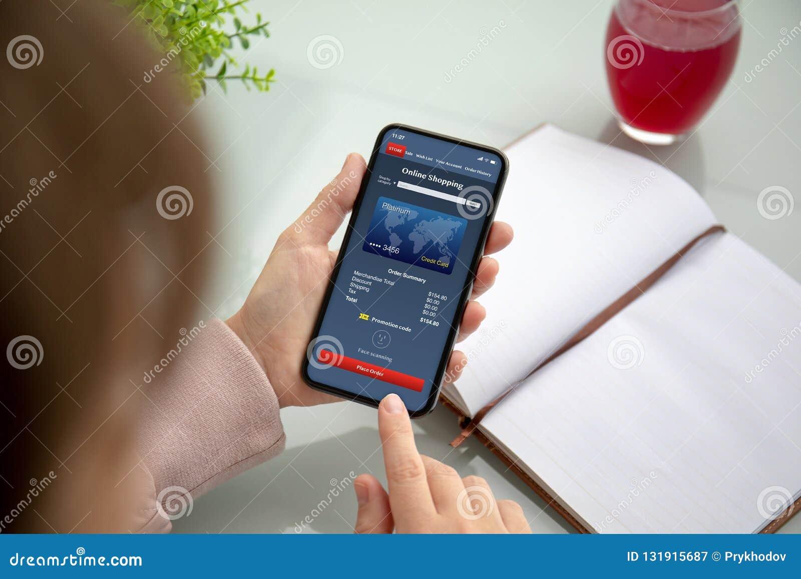 Kobieta wręcza mienie telefon z app online zakupy na ekranie
