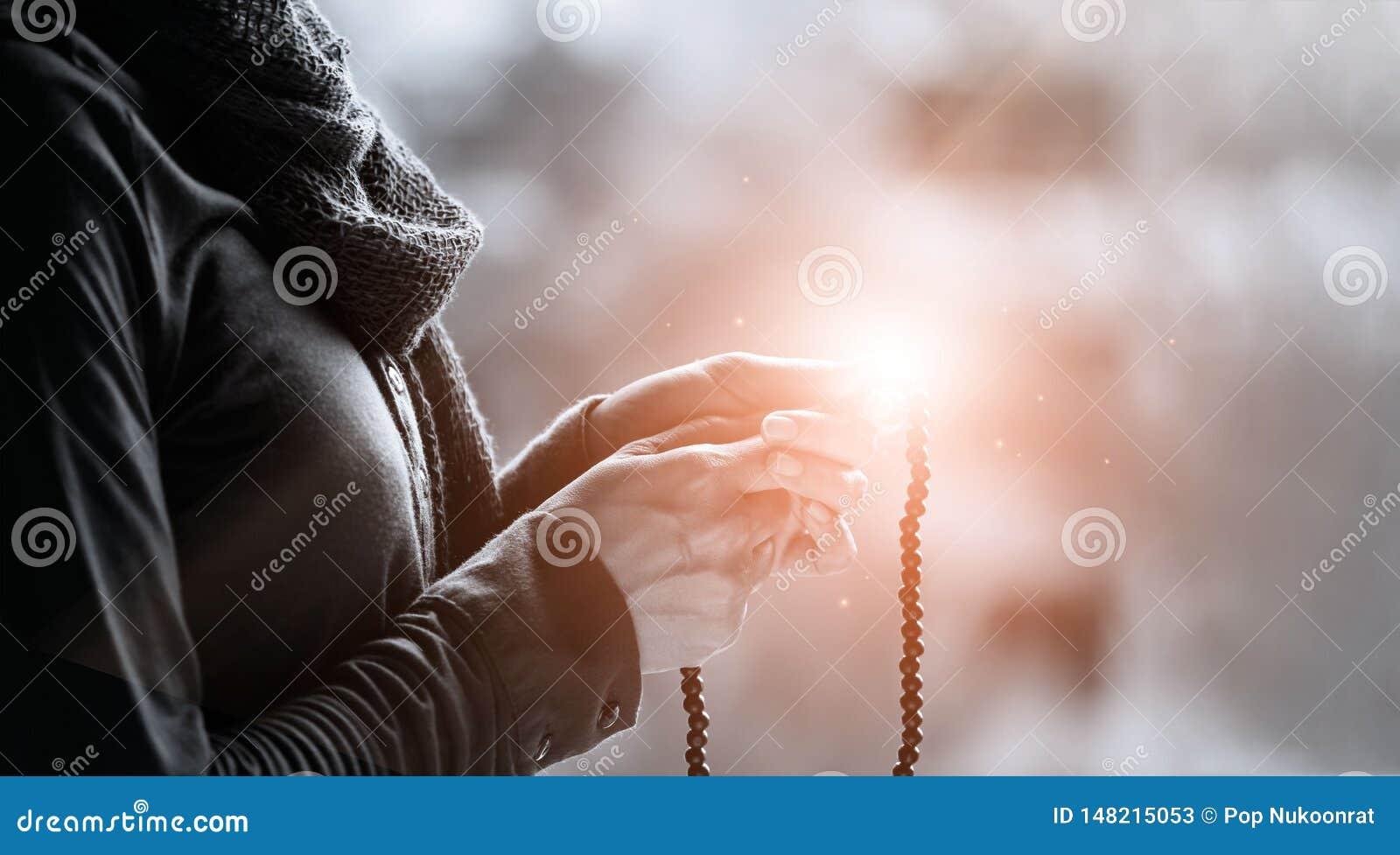Kobieta wr?cza modlenie i mienia koralika r??aniec na o?wietleniowych backgrouns, black&white, wiary religijnej poj?cie