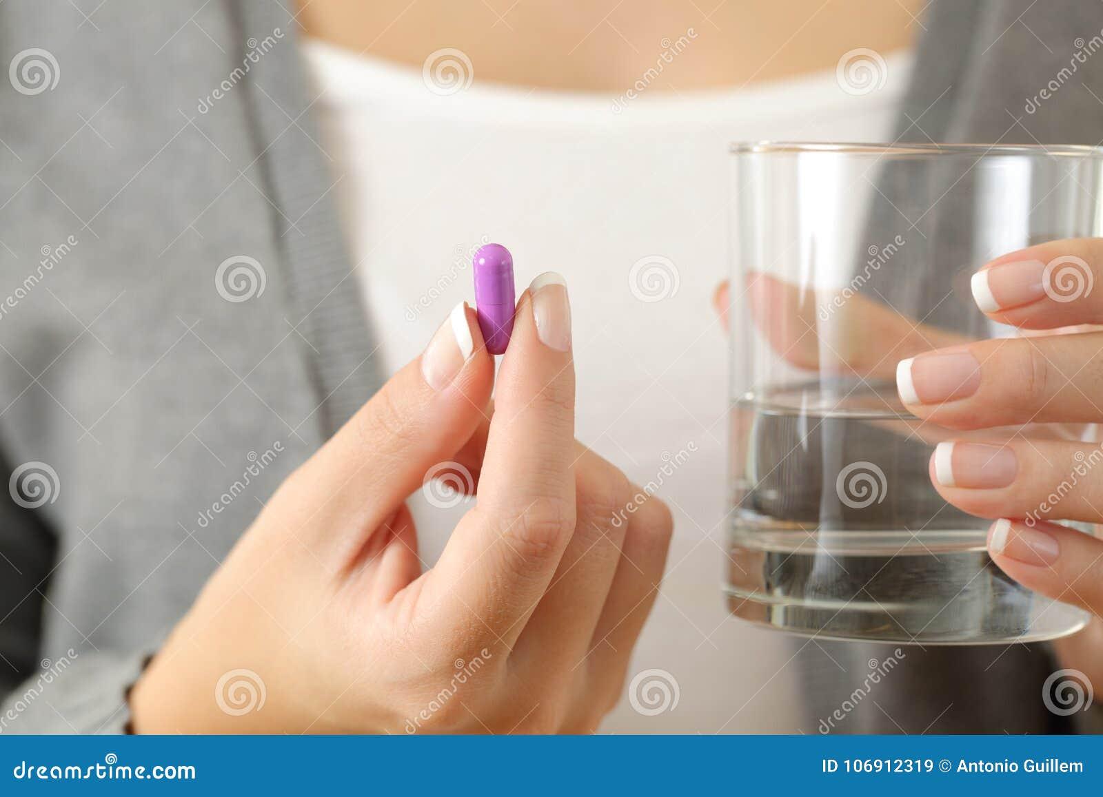 Kobieta wręcza trzymać pigułkę i szkło woda