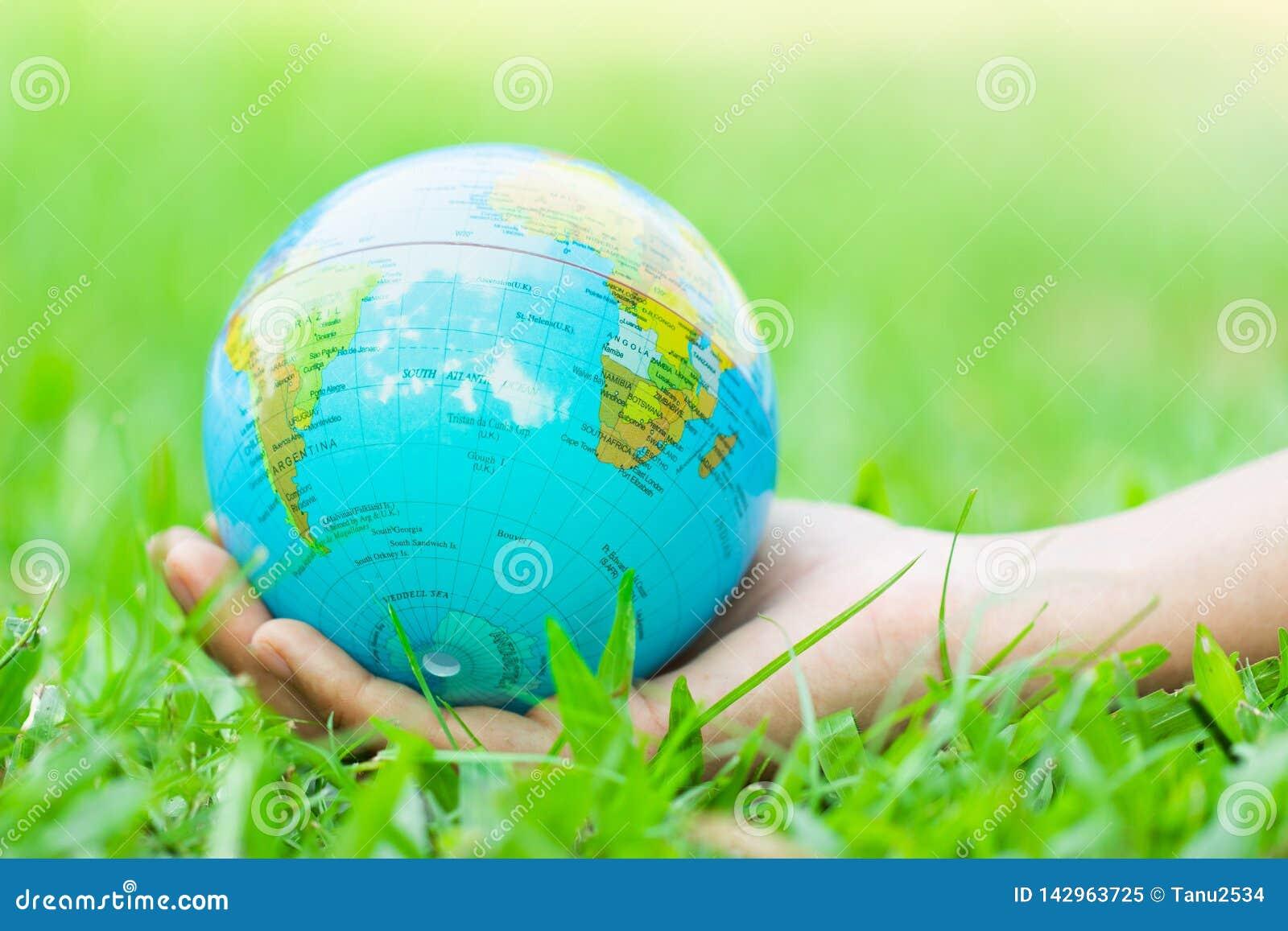 Kobieta wręcza trzymać spławową ziemię na naturalnym zielonym tle