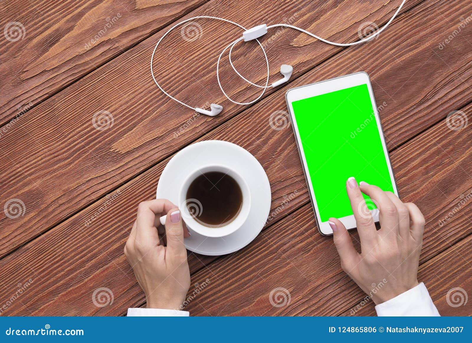 Kobieta wręcza używać mockup cyfrowi pastylki, filiżanki kawy i białych hełmofony na brown drewnianym biurku, odgórny widok