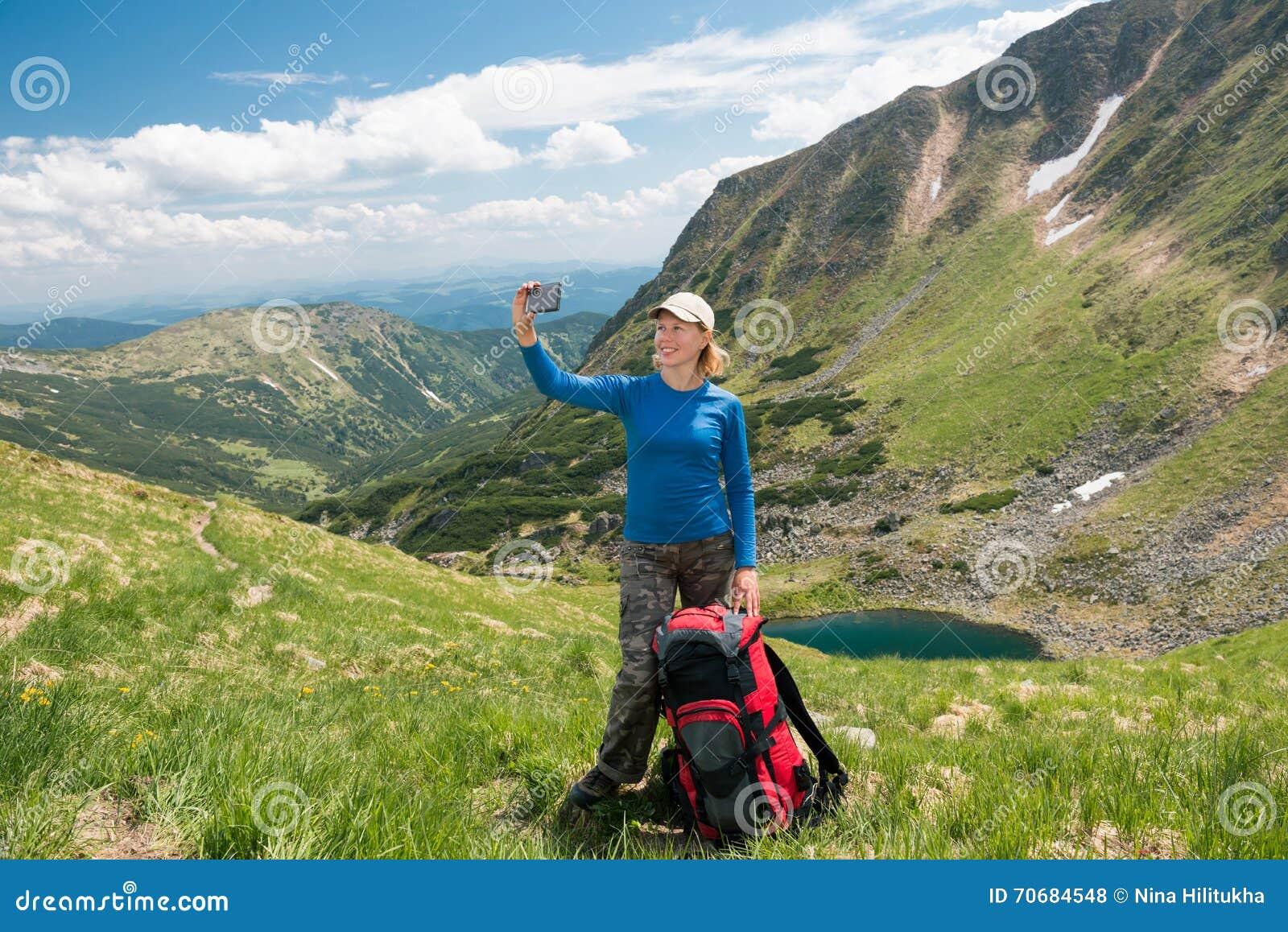 Kobieta wycieczkowicz bierze selfie z smartphone w górach