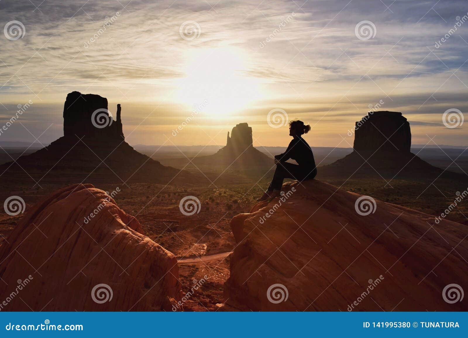 Kobieta wycieczkowicz ogląda piękną scenerię wschód słońca w Pomnikowej dolinie, Utah, usa