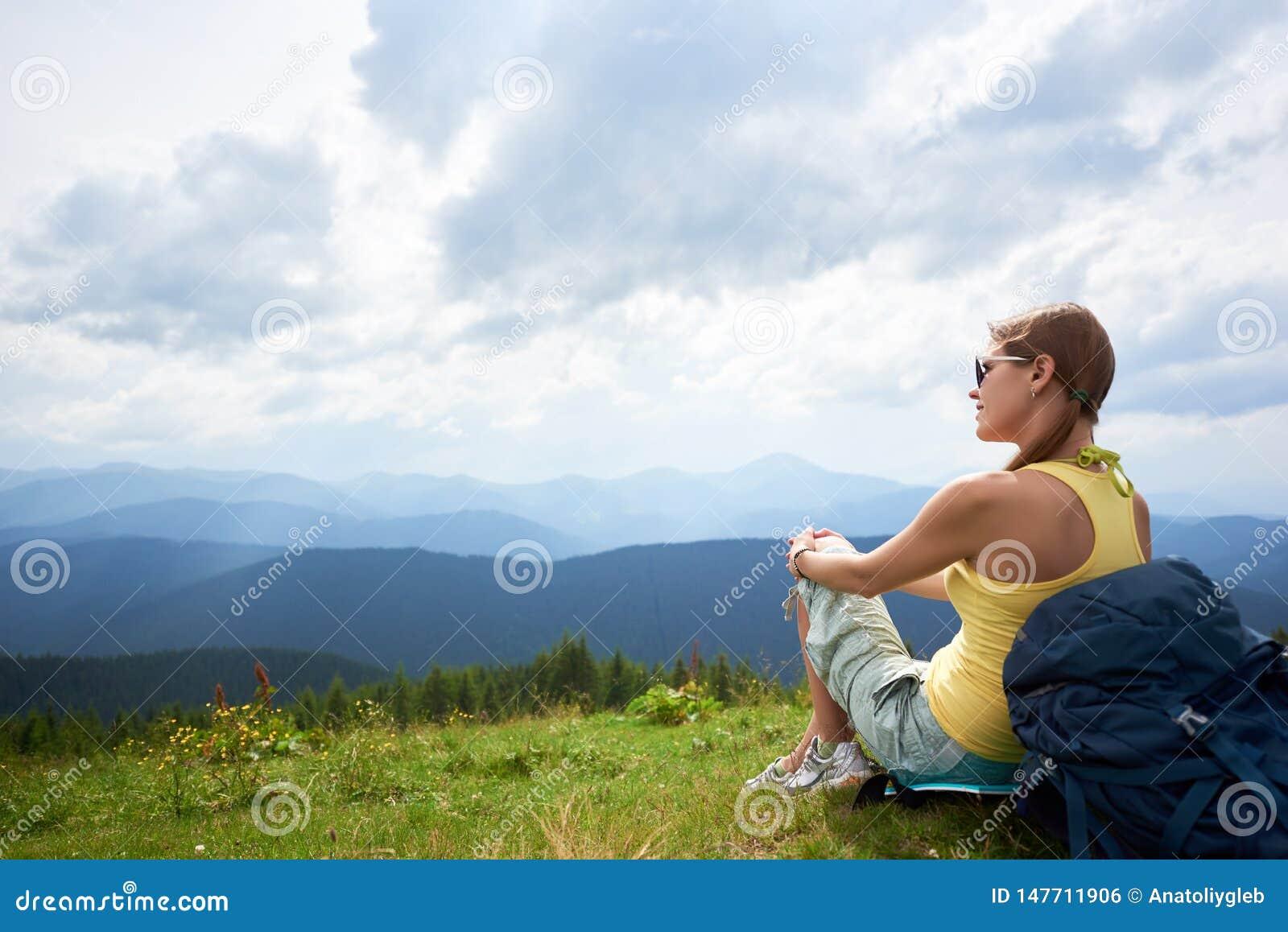 Kobieta wycieczkowicz wycieczkuje na trawiastym wzg?rzu, b?d?cy ubranym plecaka, u?ywa trekking wtyka w g?rach