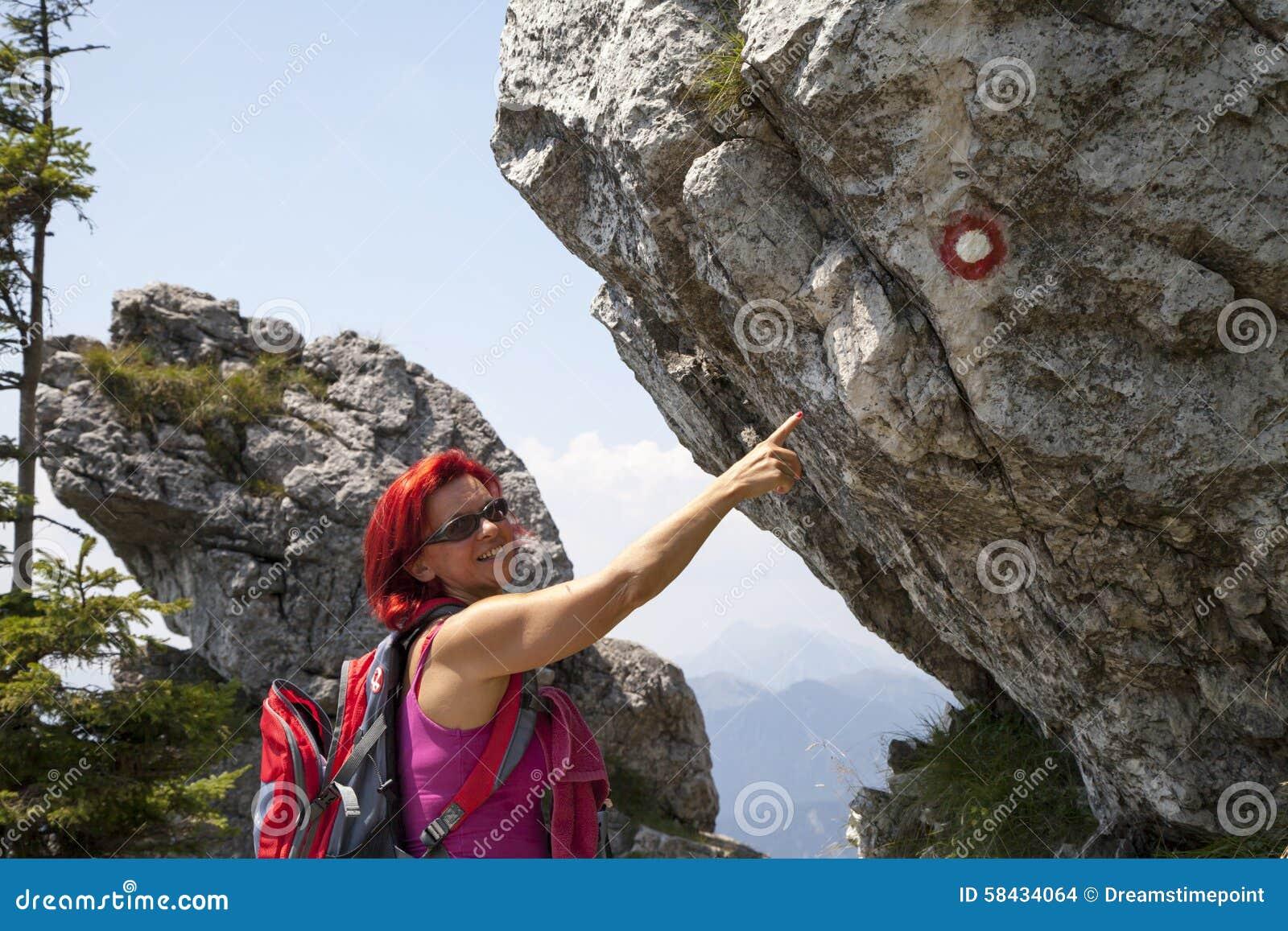 Kobieta wycieczkowicz wysoki w górze wskazuje szyldowa poczta