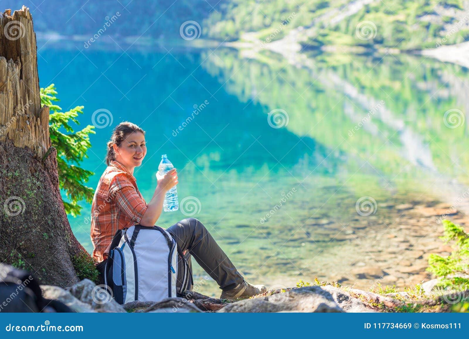 Kobieta z butelką woda pitna odpoczywa blisko pięknego sce