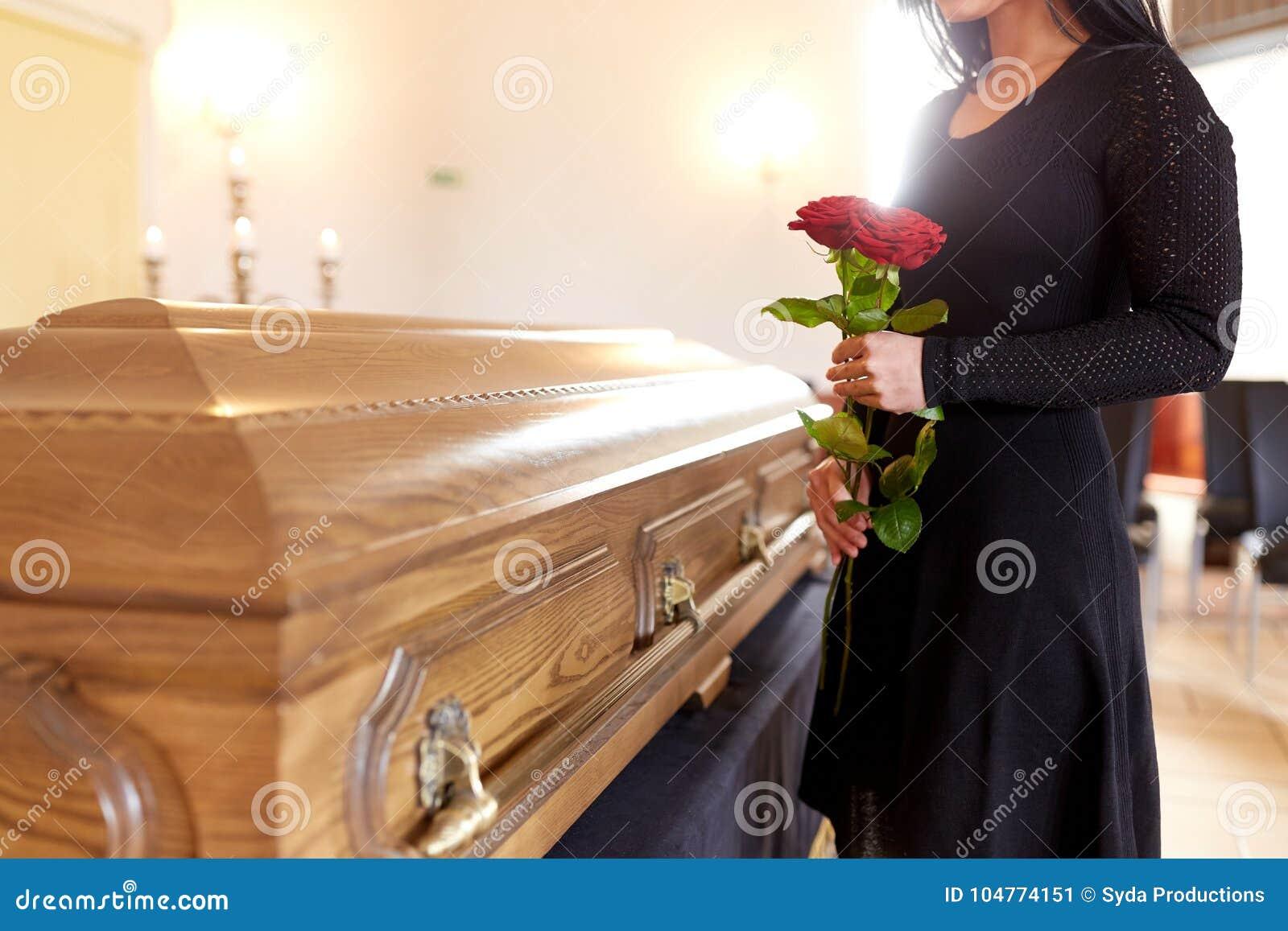 Kobieta z czerwonymi różami i trumną przy pogrzebem