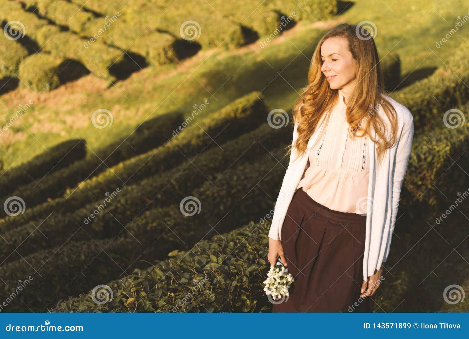 Kobieta z długie włosy z bukietem kwiaty śnieżyczki na tle herbaciana plantacja