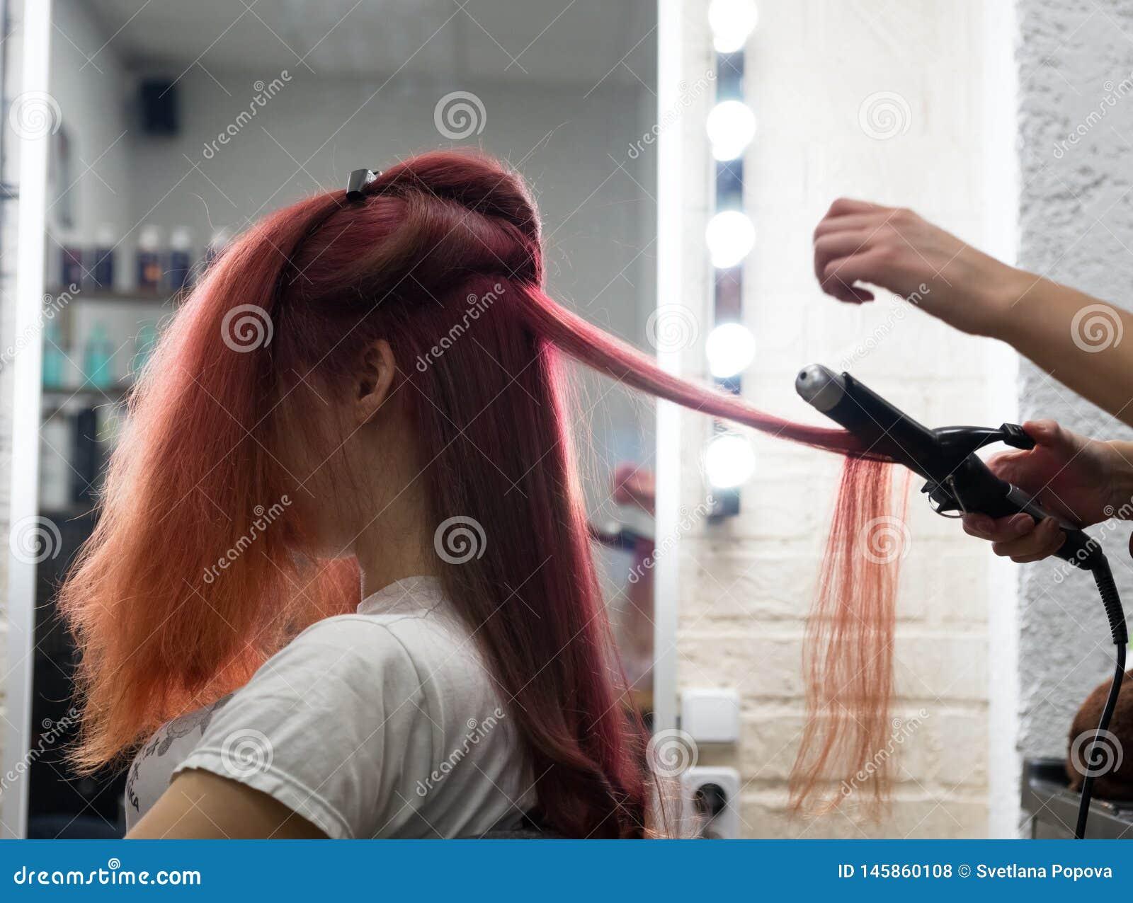 Kobieta z długie włosy obsiadaniem na fryzowanie procedurze fryzuje używać fryzowań żelaza w salonu fryzjerze