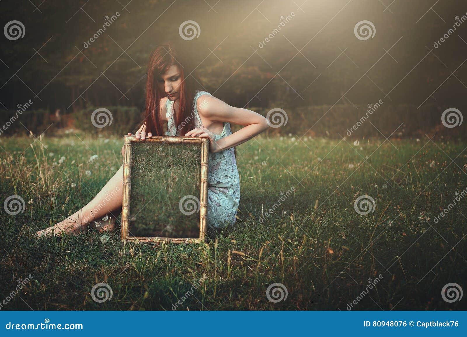Kobieta z dziwacznym lustrem na łące
