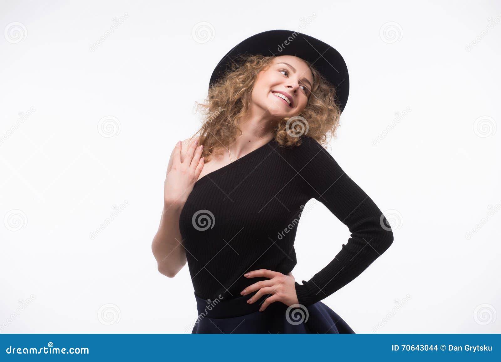 Kobieta z kędzierzawym włosy w czarnym kapeluszu i eleganckiej eleganckiej wieczór sukni