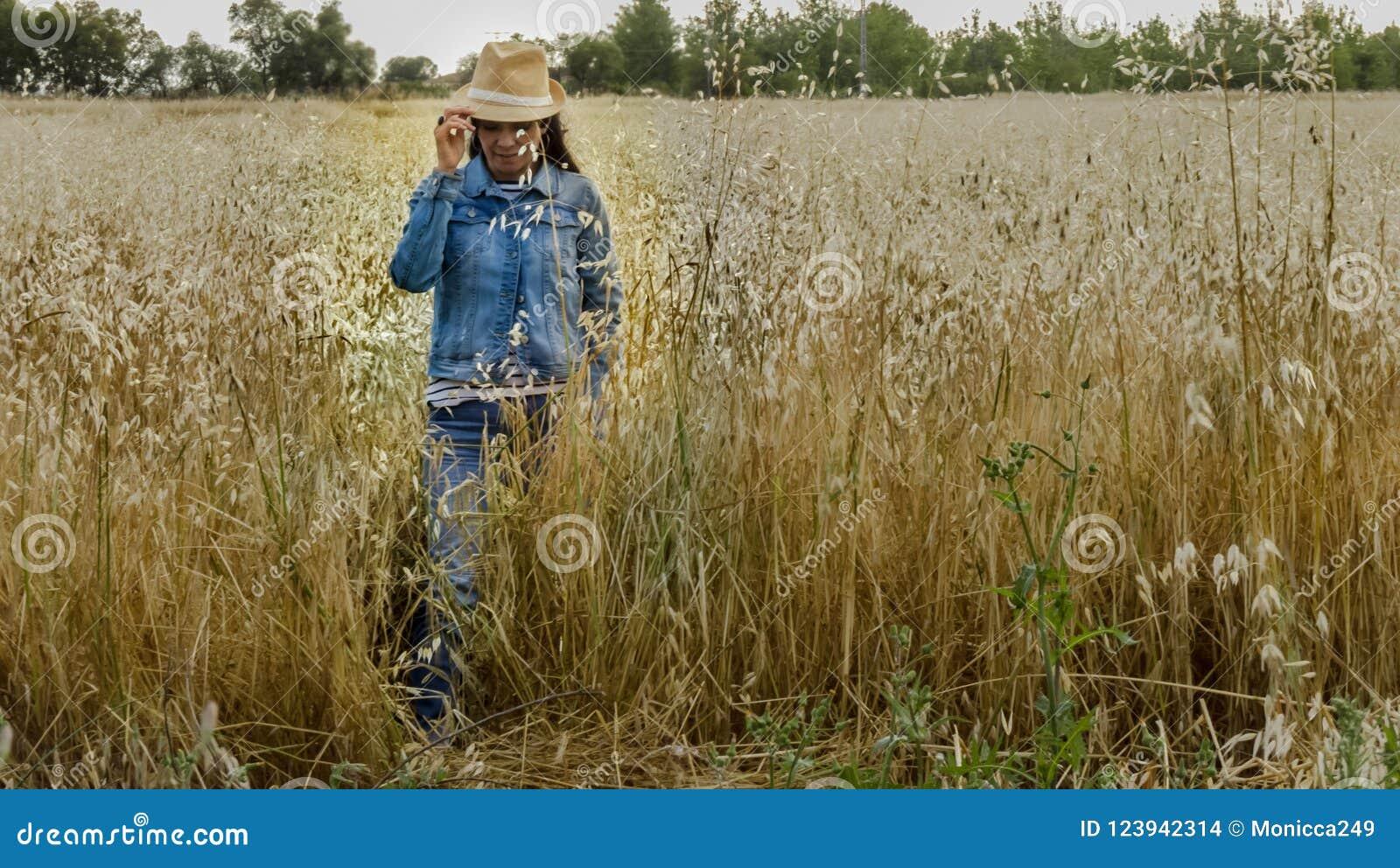 Kobieta z kapeluszem w pszenicznym polu, szczęśliwa kobieta