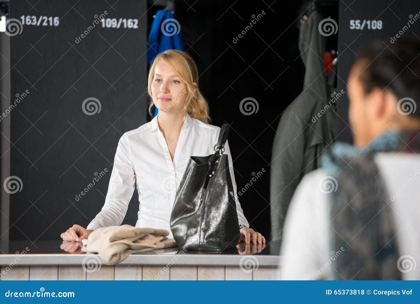 Kobieta Z kiesy pozycją Przy torba depozytu kontuarem