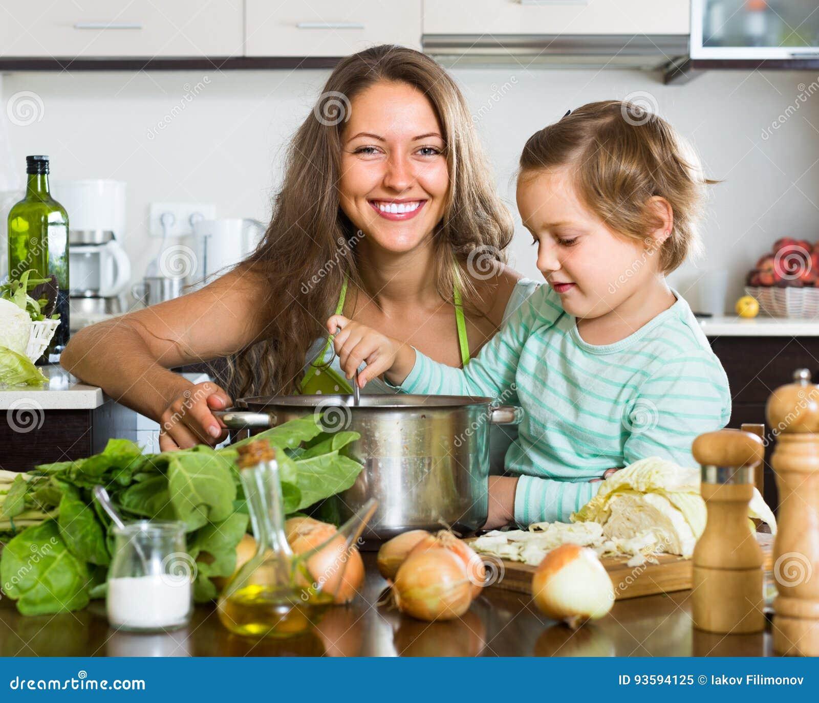 Kobieta z małą dziewczynką gotuje w domu