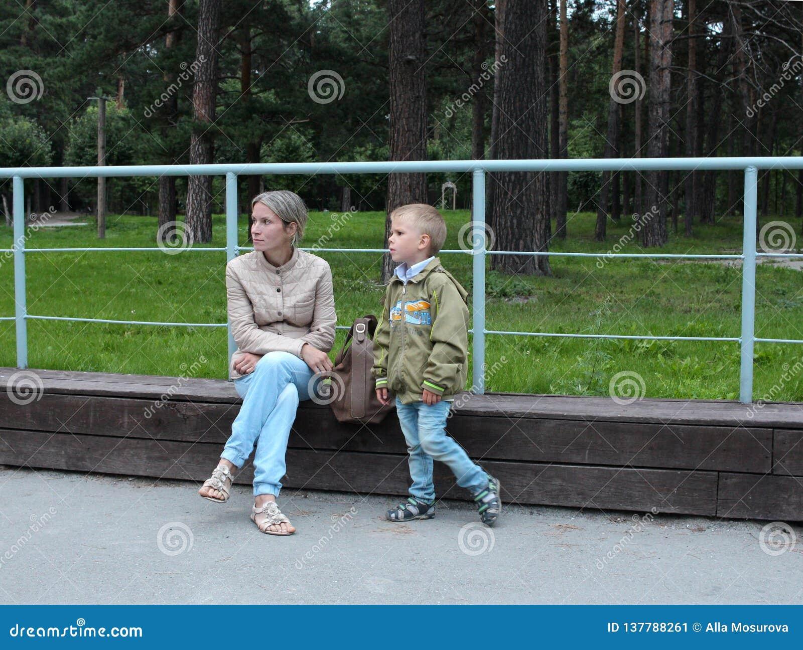 Kobieta z małym chłopiec dziecka odprowadzeniem w Parkowym obsiadaniu na ławki odpoczywać