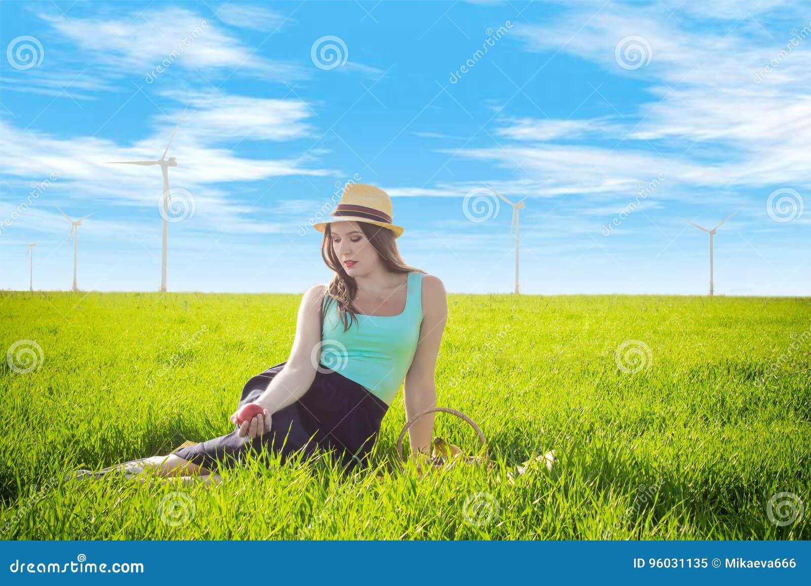Kobieta z owocowymi pobliskimi wiatrowymi generatorami