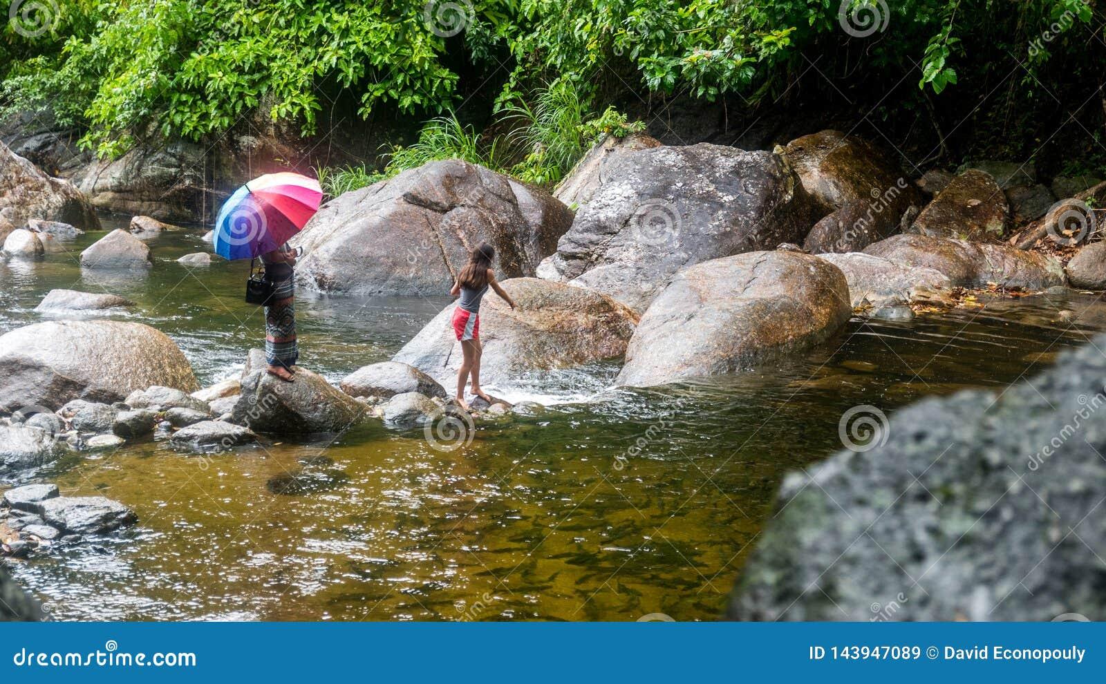 Kobieta z parasolem i dziewczyn? w czerwonych skr?tach