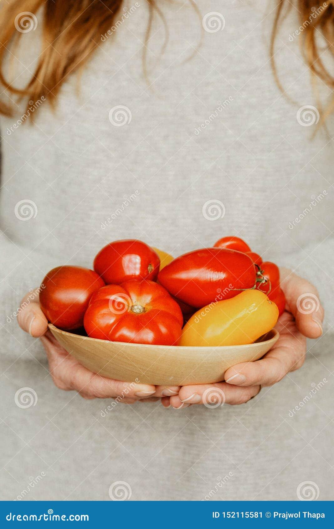Kobieta Z pucharem pomidory I pieprze