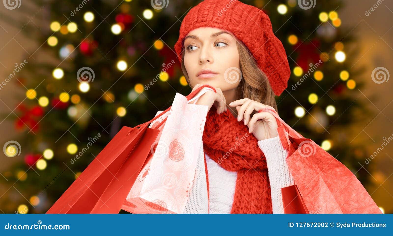 Kobieta z torba na zakupy nad bożonarodzeniowe światła