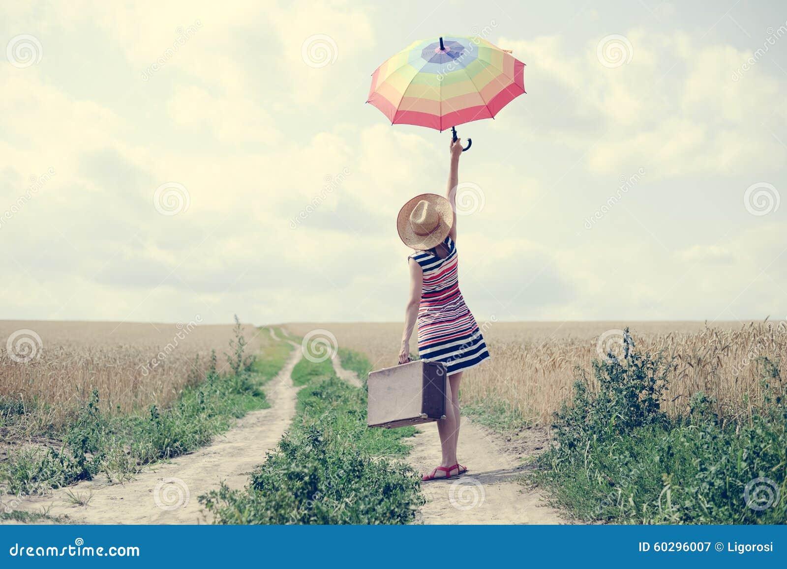 Kobieta z walizki i parasola pozycją na drodze