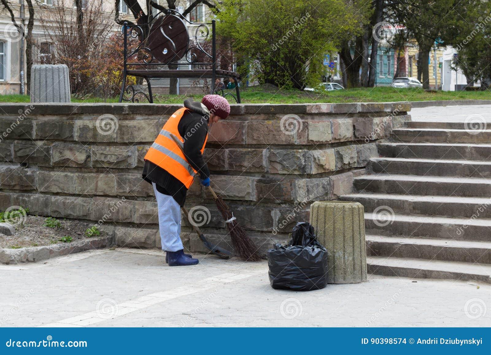 Kobieta zamiata ulicznego cleaner