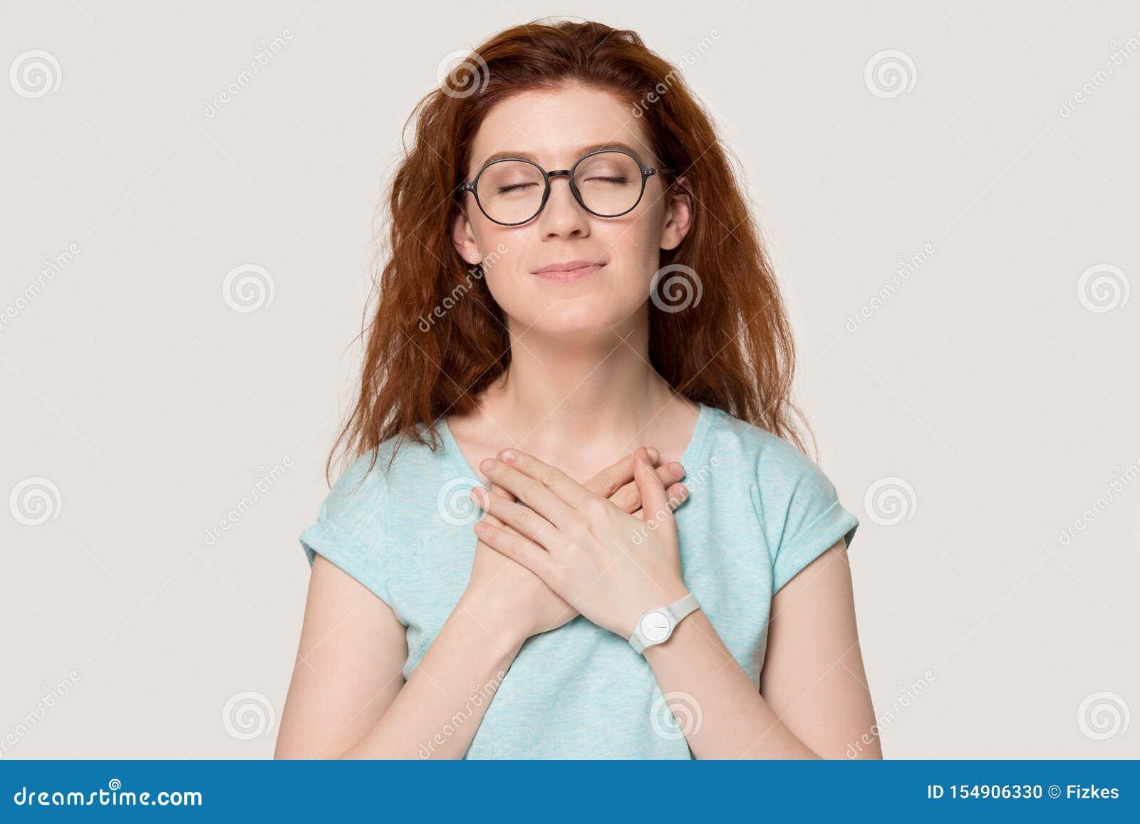Kobieta zamknięta ona oko chwytów ręki na klatce piersiowej czuje wdzięczność