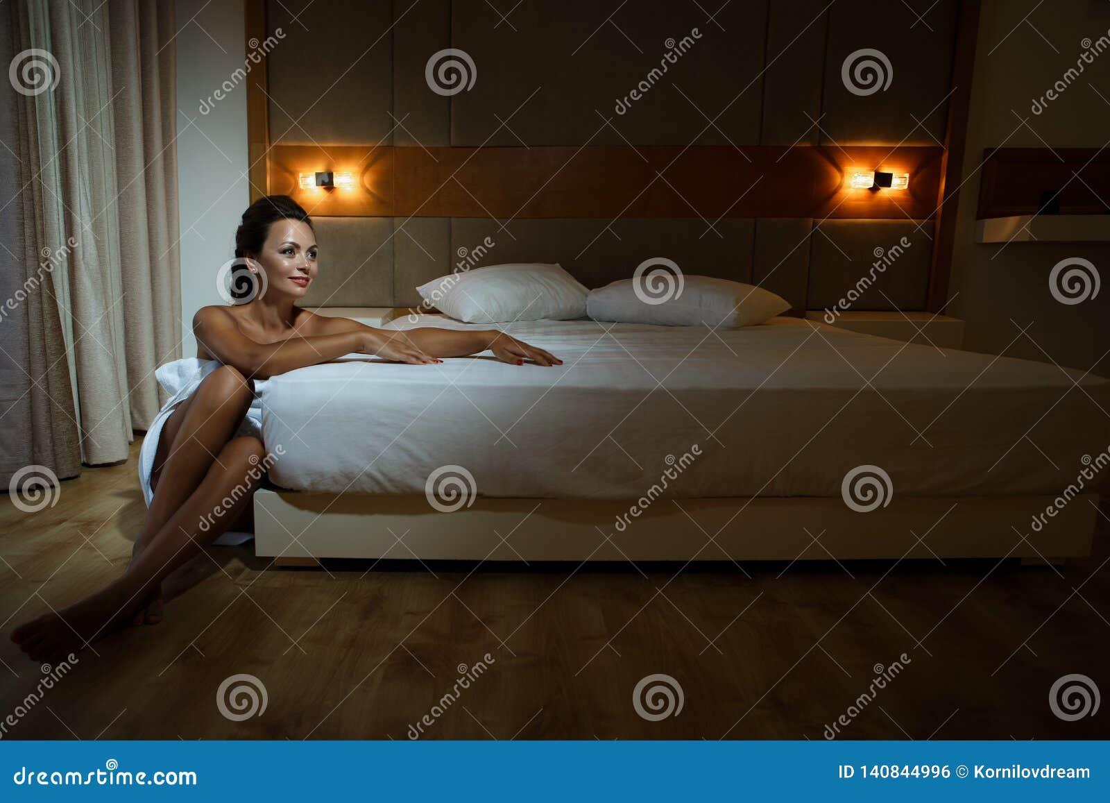 Kobieta zawijająca w kąpielowym ręczniku siedzi następnego łóżko