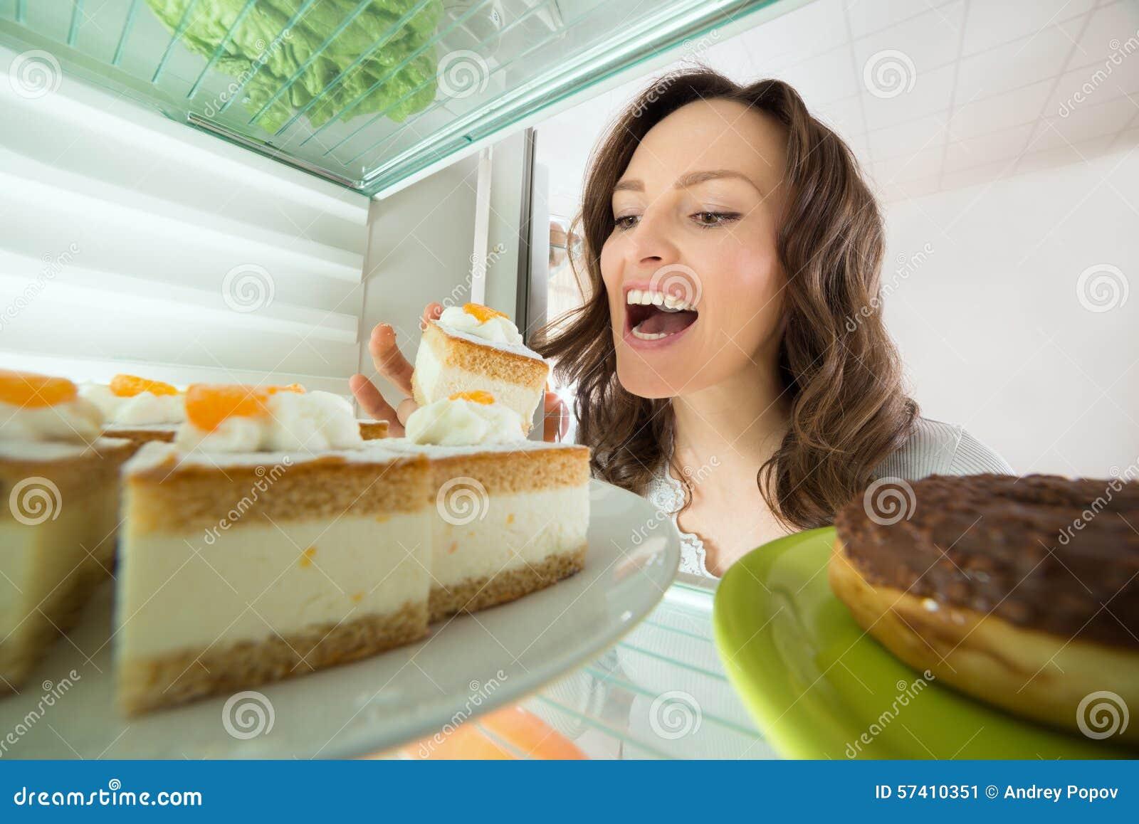 Kobiety łasowania plasterek tort Od Fridge