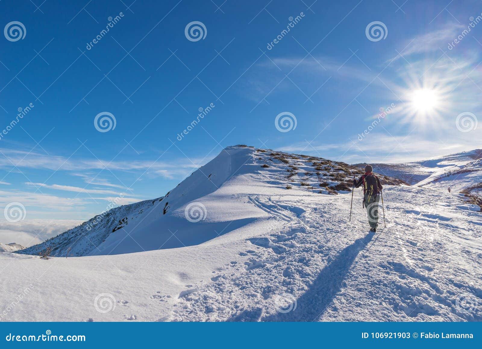 Kobiety backpacker trekking na śniegu na Alps Tylni widok, zima styl życia, zimny uczucie, słońce gwiazda w backlight