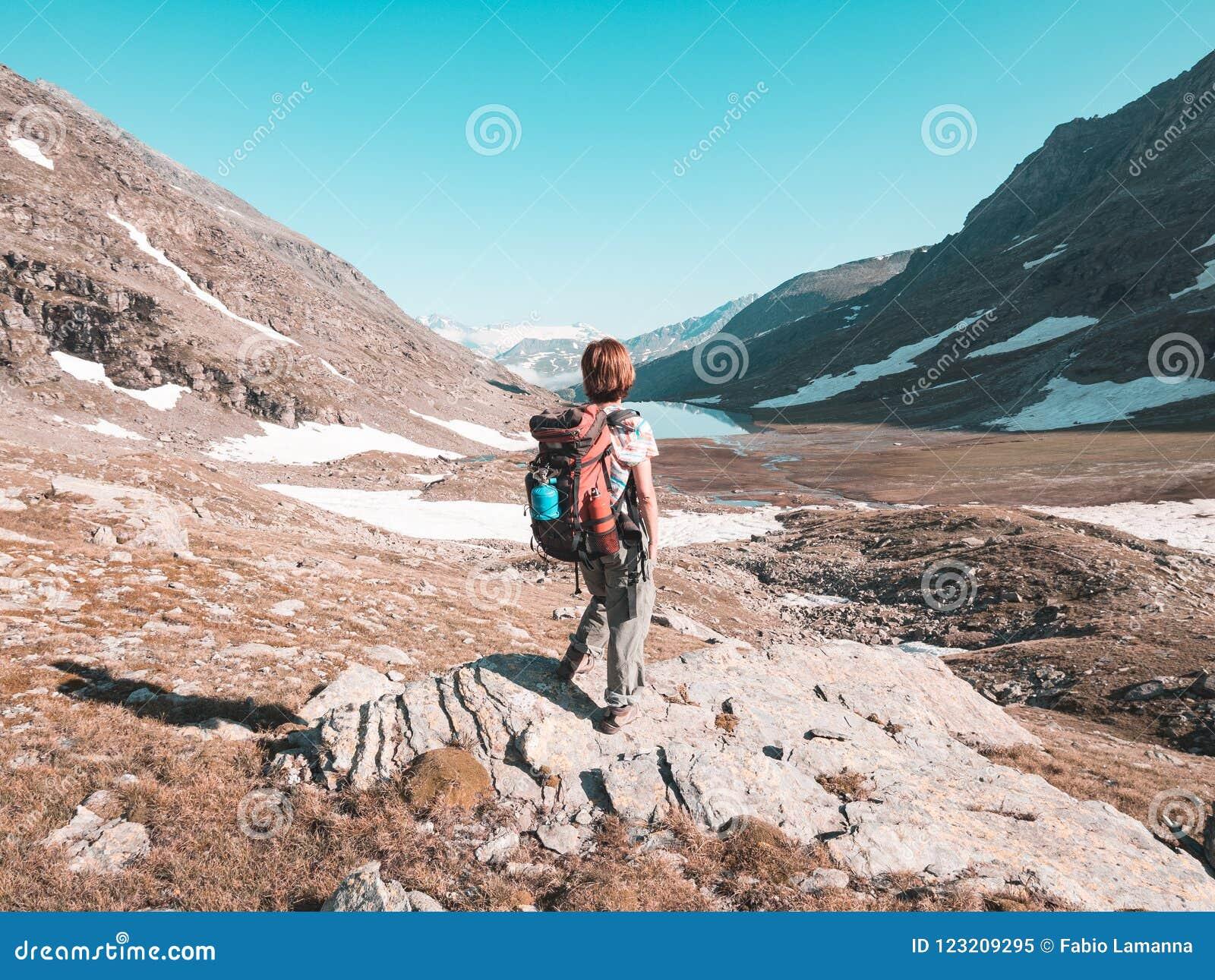 Kobiety Backpacker wycieczkuje w idyllicznym krajobrazie, siklawie i kwitnącej łące, Lato eksploracja na Alps i przygody stonowan