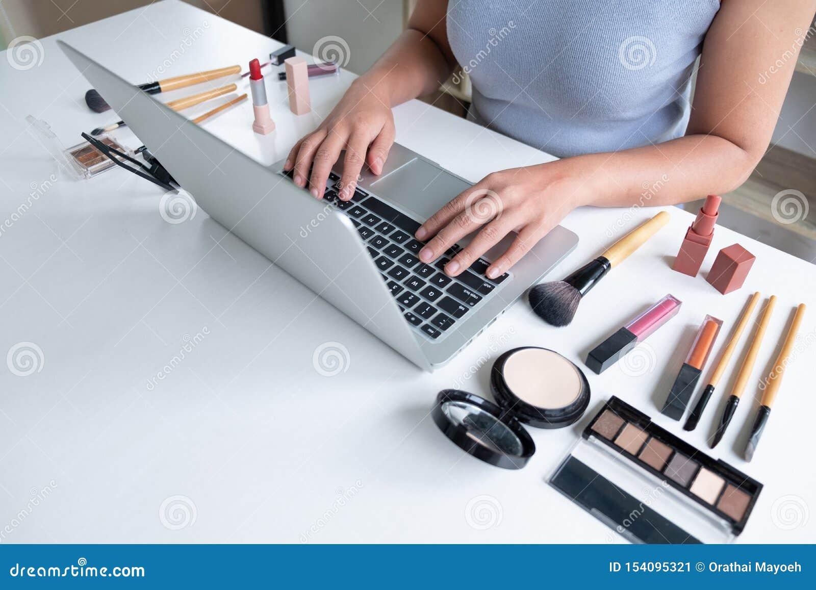 Kobiety blogger teraźniejszości produktu kosmetyczny obsiadanie w frontowej pastylce i transmisji ogólnospołeczna sieć internetem