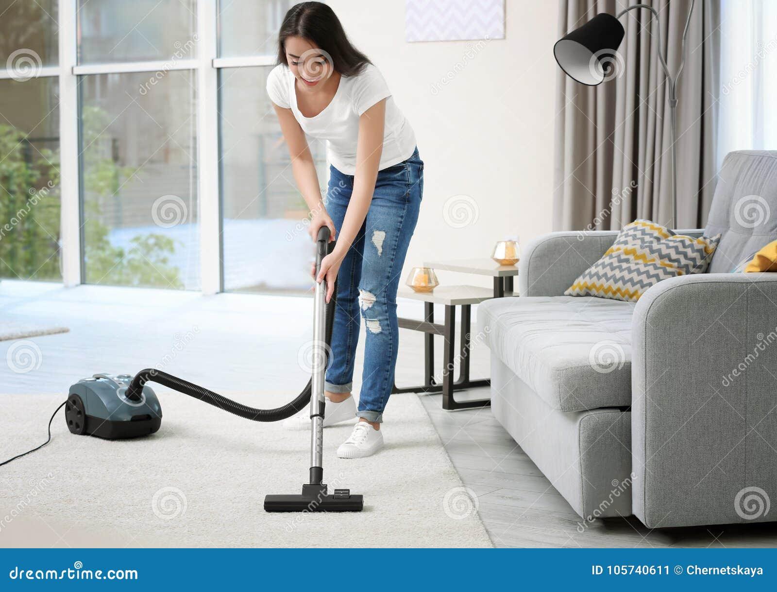Kobiety cleaning dywan z próżnią w pokoju