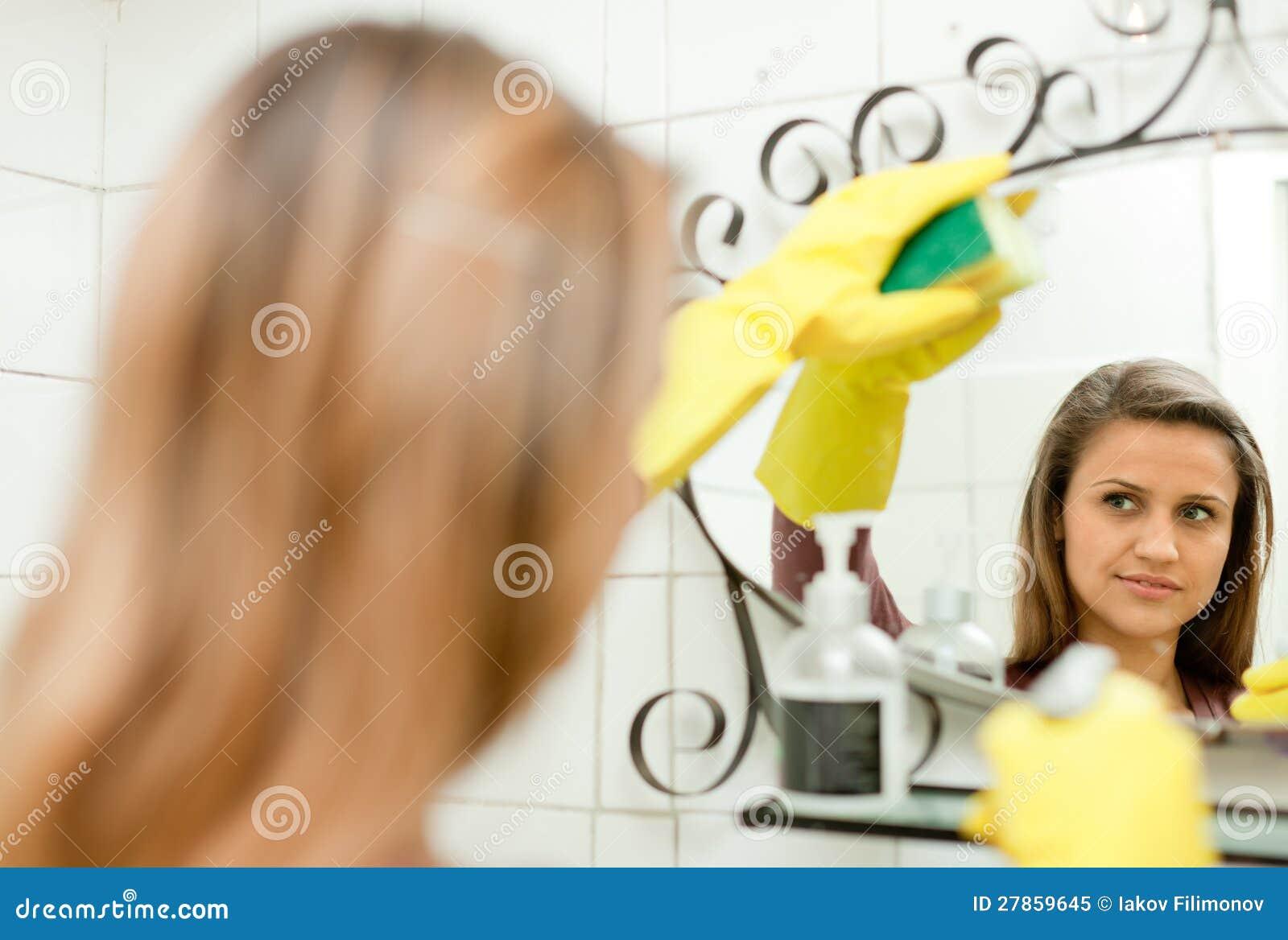 Kobiety cleaning lustro w łazience