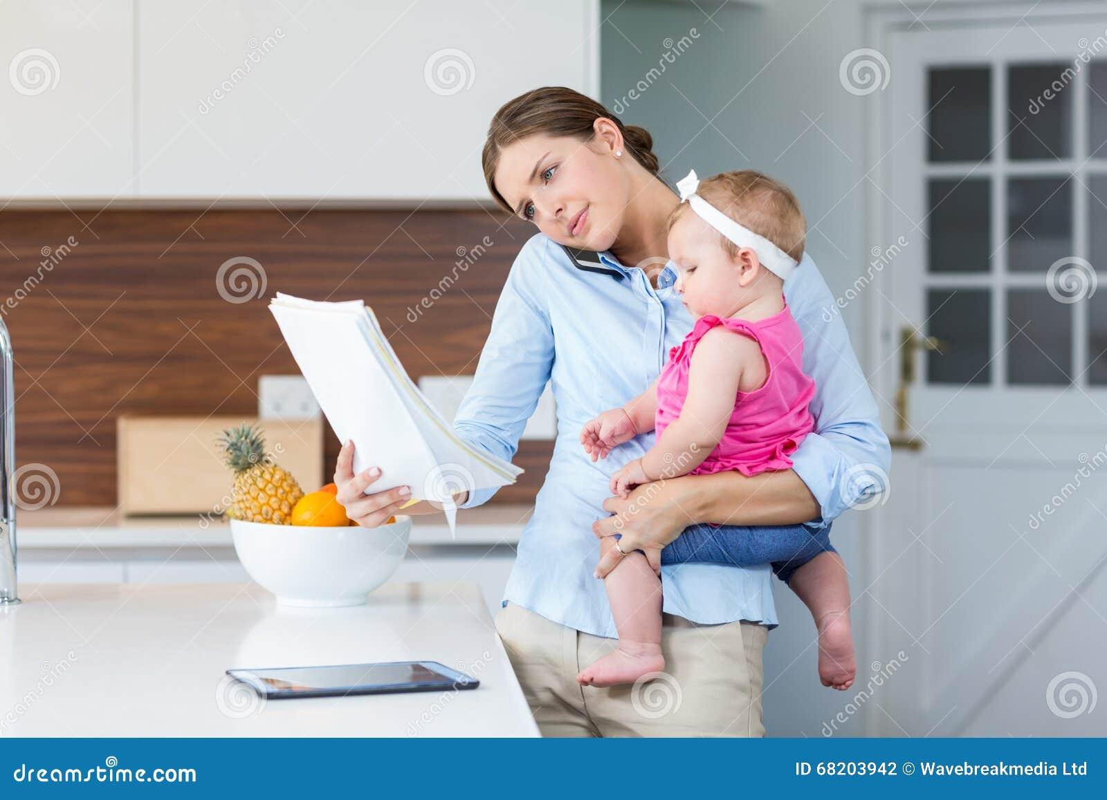 Kobiety czytania dokumenty podczas gdy niosący dziewczynki