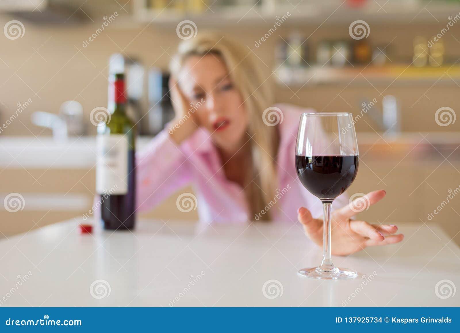 Kobiety dojechanie dla szkła wino podczas gdy samotnie w domu