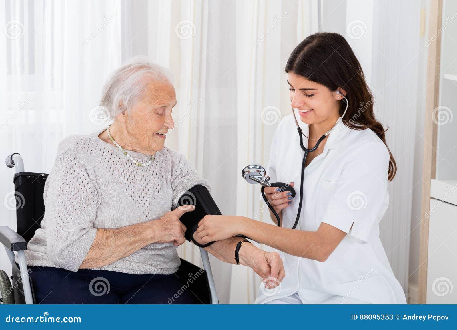 Kobiety doktorski sprawdza ciśnienie krwi starsza kobieta