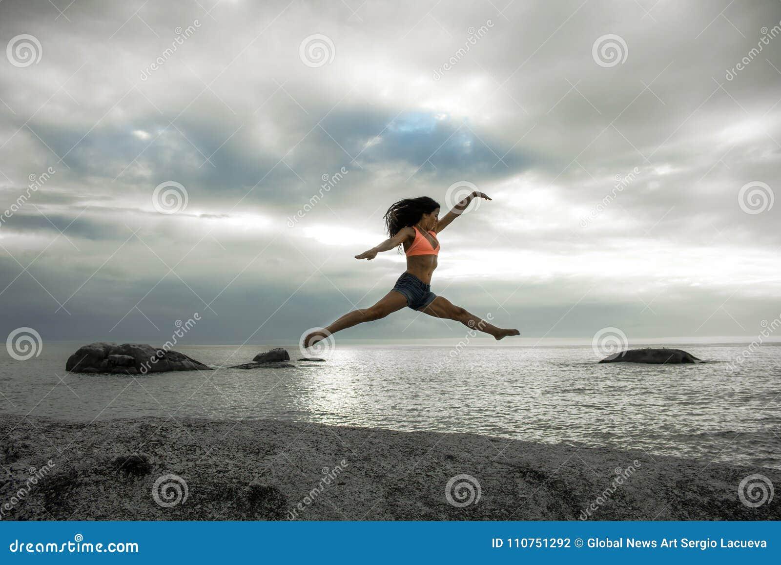 Kobiety doskakiwanie na skale przy zmierzchem na Bakovern plaży, Kapsztad