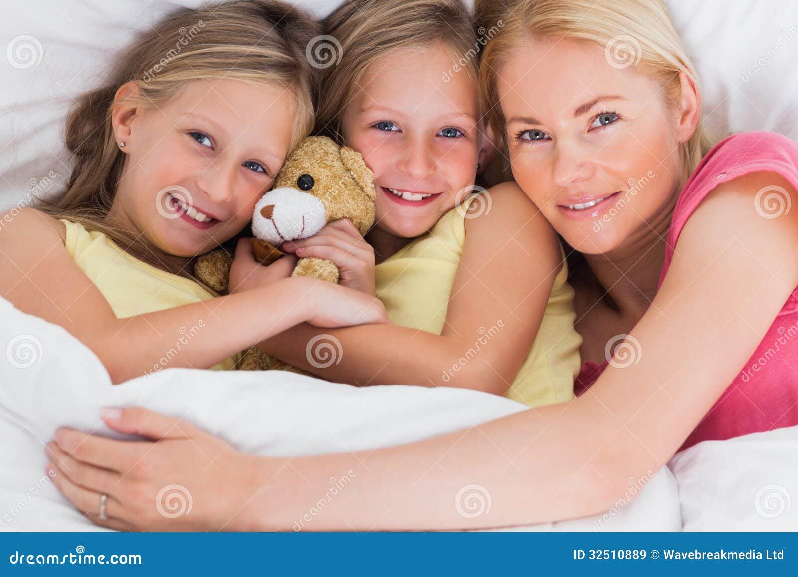 Kobiety drzemanie w łóżku z jej ślicznymi dziećmi