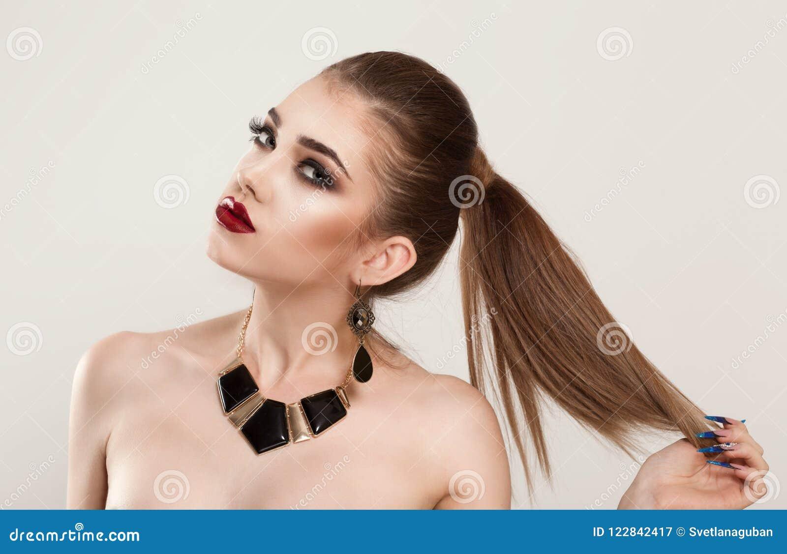 Kobiety dziewczyna trzyma jej włosy, chce pokazywać jej fryzury brązowi włosianego kolor