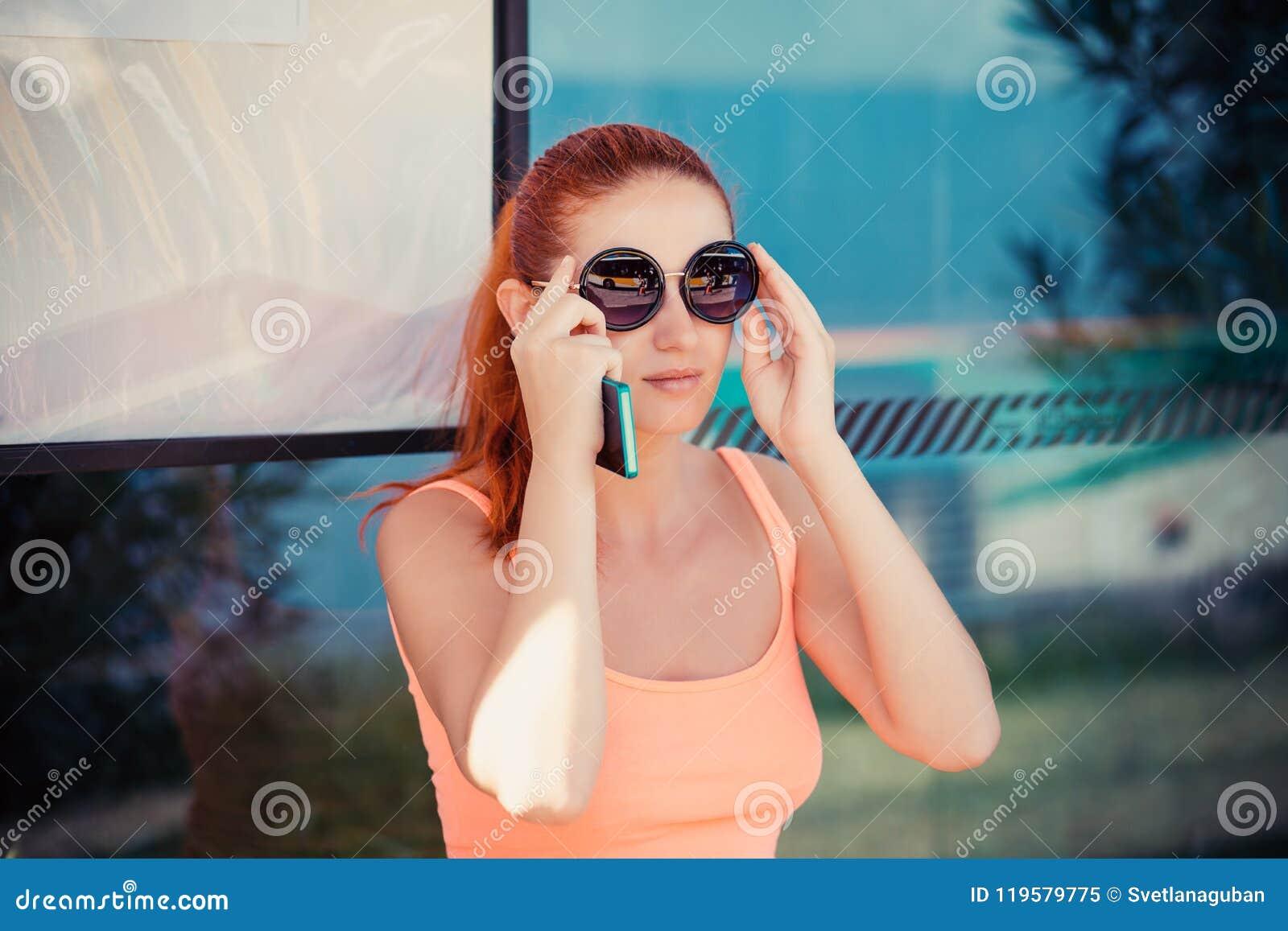 Kobiety dziewczyny żeński obsiadanie w przystanku autobusowym przystosowywa wokoło okularów przeciwsłonecznych
