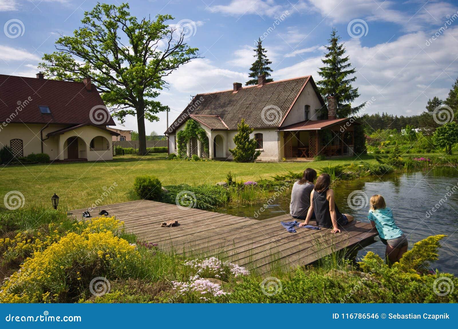 Kobiety i dziewczyny obsiadanie wioska domu basenem