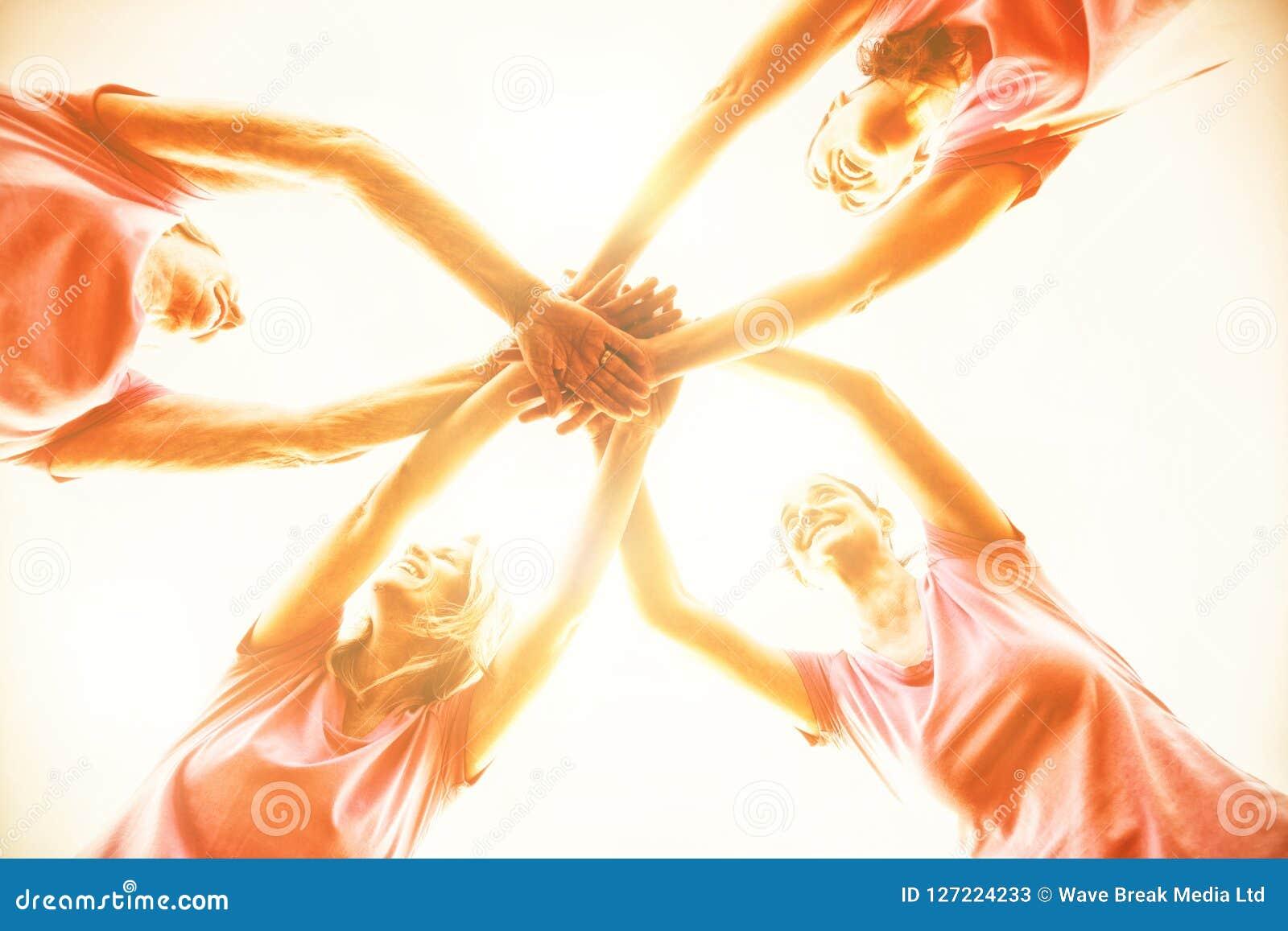 Kobiety jest ubranym różowe koszulowe kładzenie ręki wpólnie