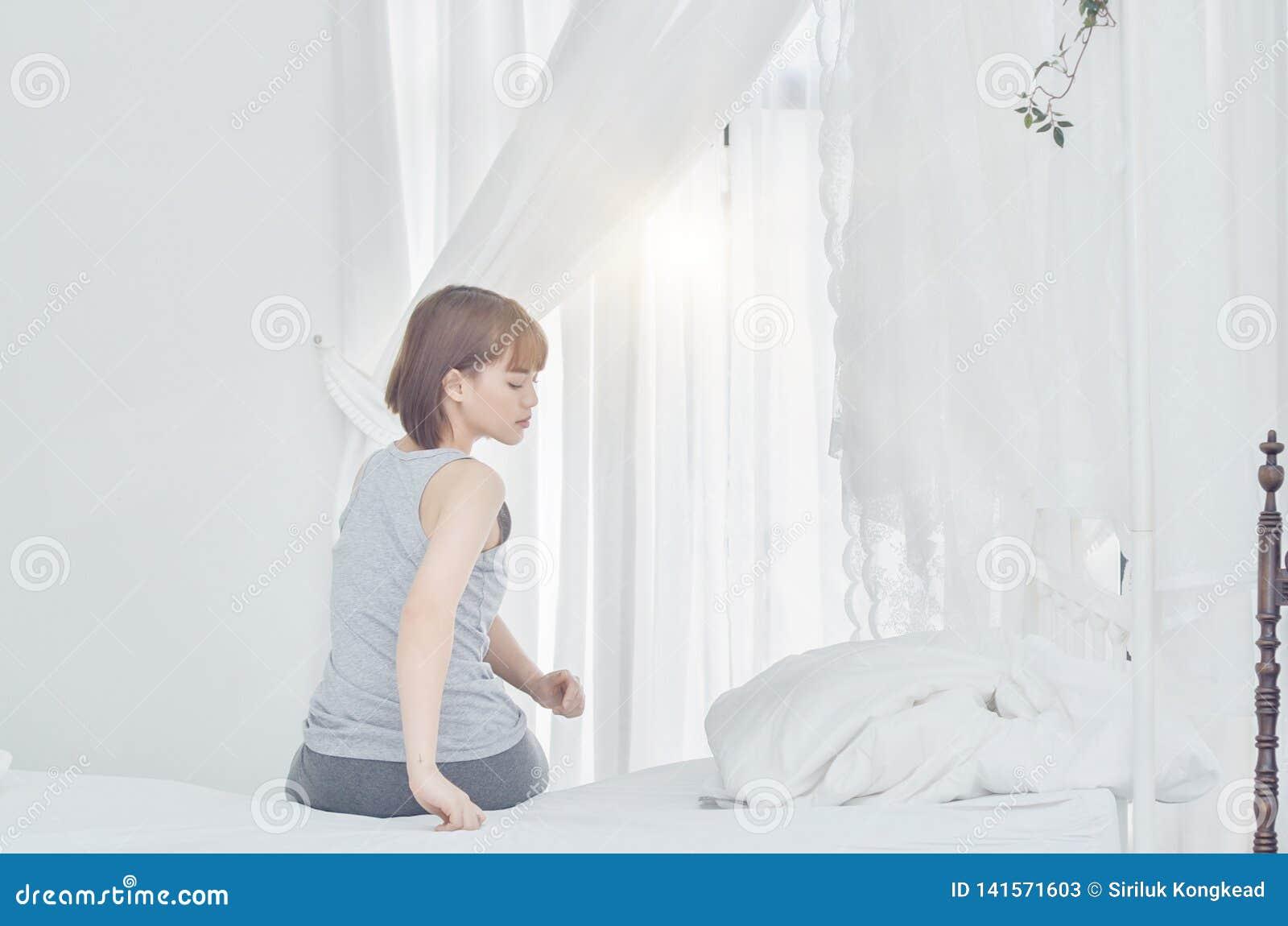 Kobiety jest ubranym szare piżamy siedzi na leżance Używają rękojeść stopa