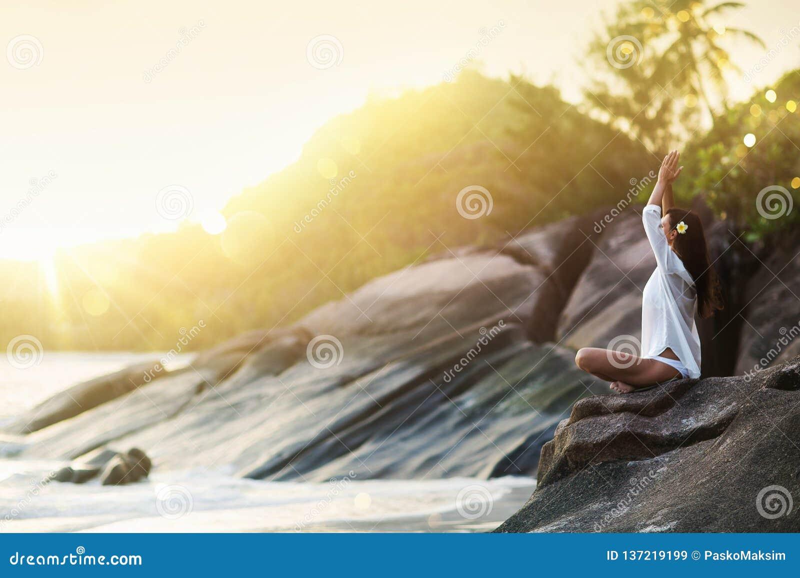 Kobiety joga Medytuje na skale na ocean plaży