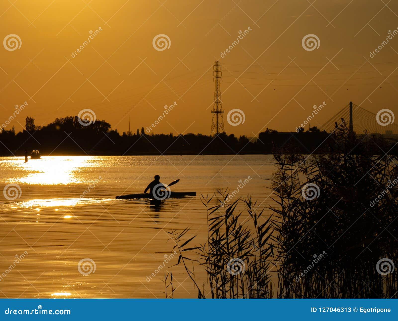 Kobiety kajakarstwo przy zmierzchem na Vistula rzece, Polska Zadziwiająca sceneria i kolory