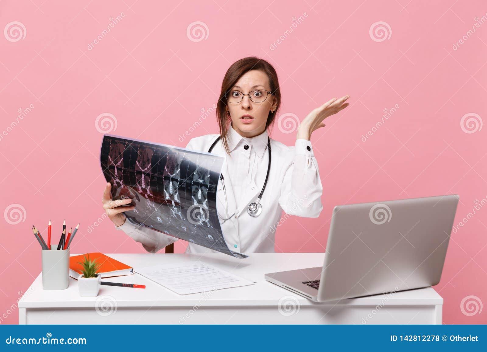 Kobiety lekarka siedzi przy biurko pracą na komputerze z medycznym dokumentu chwyta promieniowaniem rentgenowskim w szpitalu odiz