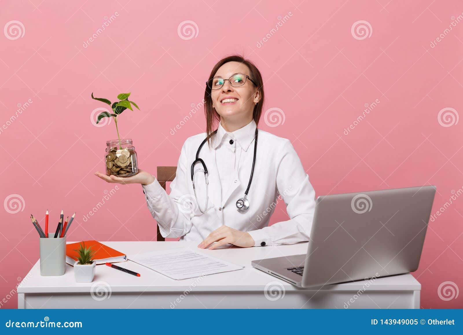 Kobiety lekarka siedzi przy biurko prac? na komputerze z medycznymi dokumentu chwyta monetami w szpitalu odizolowywaj?cym na past